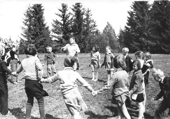На этом снимке празднование Дня Пионерии – 19 мая в селе Шабуры. Всем педагогам были даны группы для проведения игр. Нина Васильевна Русанова проводит игровое занятие с учащимися Шабурской восьмилетней школы на полянке возле школы.