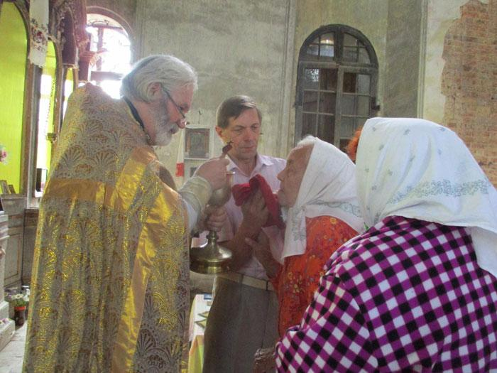 На снимке: причащает прихожан священник Василий Облецов.